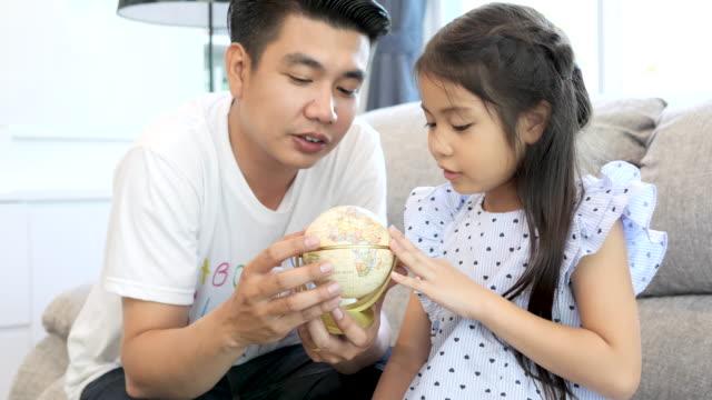 far hjälpa sin dotter lära sig med en jordglob i vardagsrummet. - förälder och barn bildbanksvideor och videomaterial från bakom kulisserna