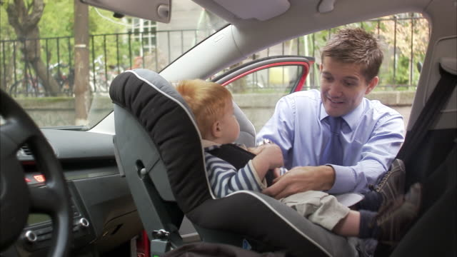 Father helping his child into the car Sweden.