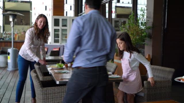 vídeos y material grabado en eventos de stock de padre ayudando a su familia sentarse en el restaurante del hotel después de que pasaron por el buffet todos buscando muy feliz - alojamiento y desayuno
