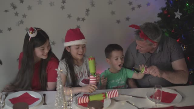 father helping his son to pull a christmas cracker - christmas cracker stock videos and b-roll footage