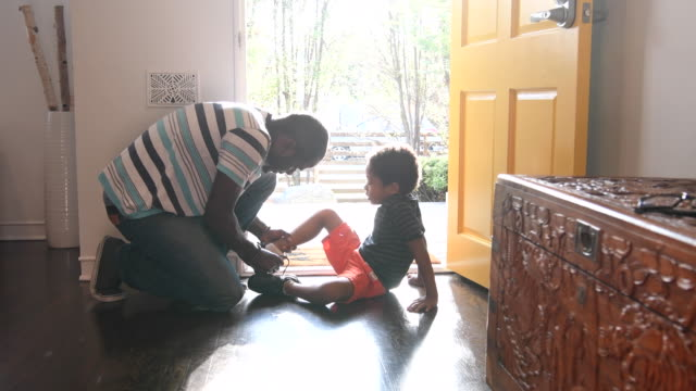 father helping his son to put shoes on in hallway - african american ethnicity stock videos & royalty-free footage