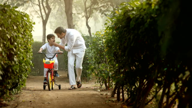 MS Father helping his son to ride bicycle in park / India