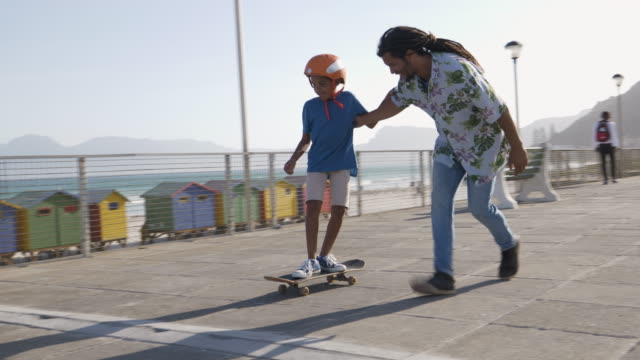 father helping his son to skateboard - skateboard stock videos & royalty-free footage