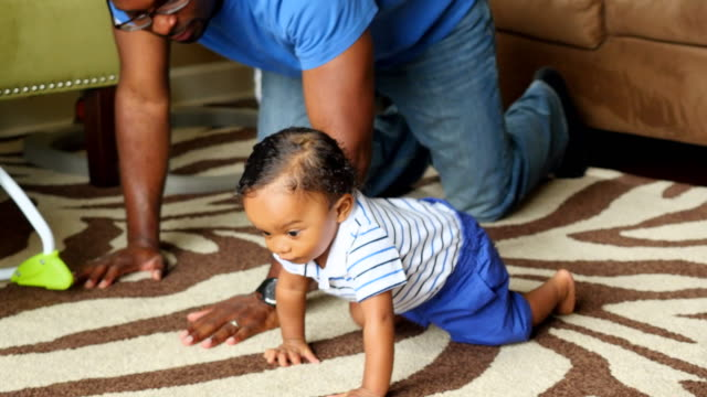 vídeos de stock, filmes e b-roll de ms father helping infant son crawl on floor in living room - engatinhando