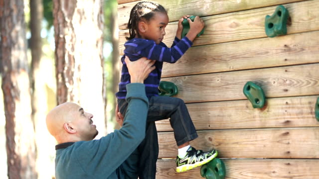 father helping little boy on climbing wall - braided hair stock videos & royalty-free footage