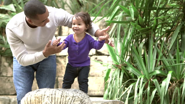 father helping little girl learning to walk - encouragement stock videos & royalty-free footage