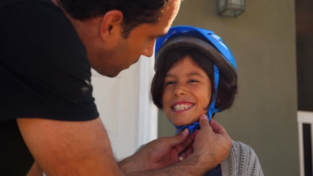 vidéos et rushes de ms father helping smiling young daughter buckle helmet before riding scooter on sidewalk - casque de vélo