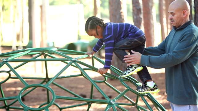 vídeos y material grabado en eventos de stock de padre ayudando a su hijo subir en la cúpula de la barra de mono - estructura metálica para niños