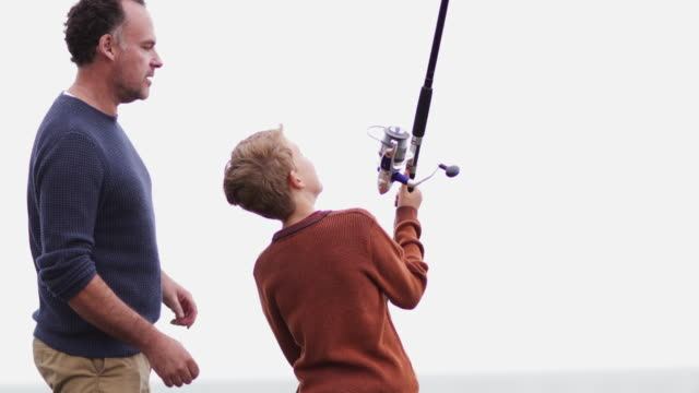 father helping son fish - fishing rod stock videos & royalty-free footage