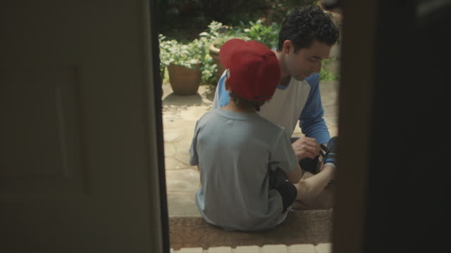 father helping son put on shoes outside - baseball sport stock videos and b-roll footage