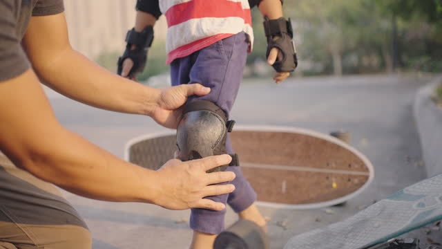 father helping son wearing protective kneepad for skateboarding. - young family stock videos & royalty-free footage