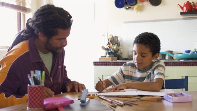 vídeos de stock, filmes e b-roll de father helping son with his homework at home - filho