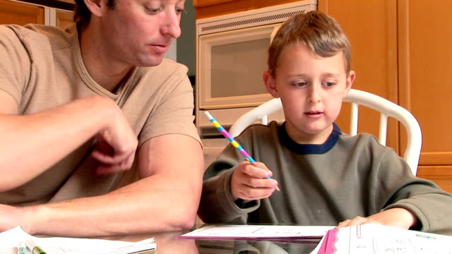 father helping son with homework - writing instrument stock videos & royalty-free footage