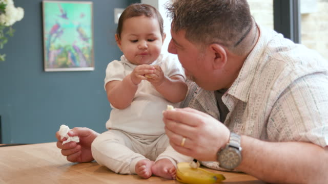 赤ちゃんの娘にバナナを与えるのを手伝う父親 - 生後2ヶ月から5ヶ月点の映像素材/bロール