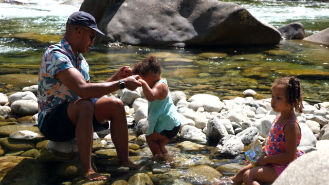 ms father helping toddler daughter balance while hanging out by river on summer afternoon - candid stock videos & royalty-free footage