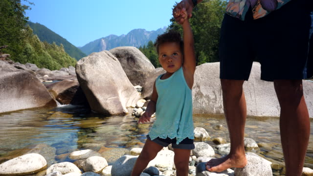 pan father helping toddler daughter walk on rock by river on summer afternoon - genderblend stock videos & royalty-free footage