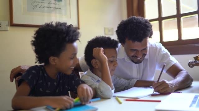 vídeos de stock, filmes e b-roll de pai ajudando dois filhos com lição de casa - caderno de anotação