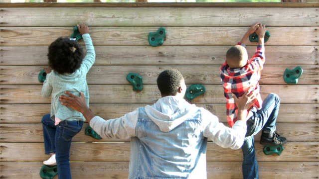father helps african-american siblings on climbing wall - reaching stock videos & royalty-free footage