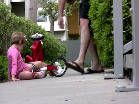 father helps child after fall - tricycle stock videos & royalty-free footage