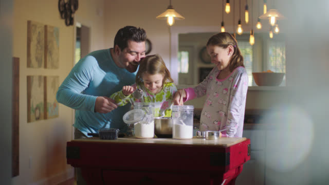 ws. father helps daughter shake flour into mixing bowl while fixing breakfast in pajamas. - genderblend video stock e b–roll
