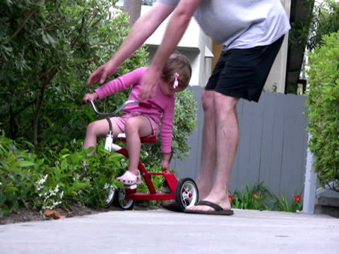 father helps daughter - tricycle stock videos & royalty-free footage