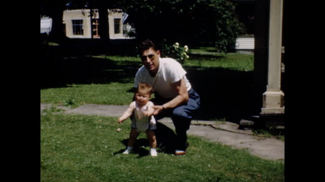 stockvideo's en b-roll-footage met a father helps his baby walk outdoors on a sunny day. - archief