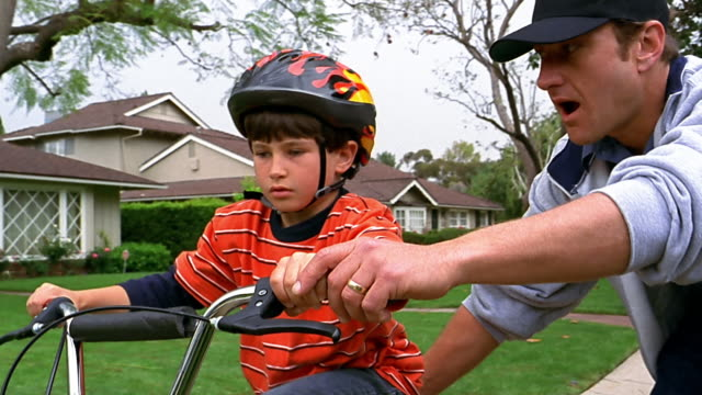 A father helps his son ride a bike.