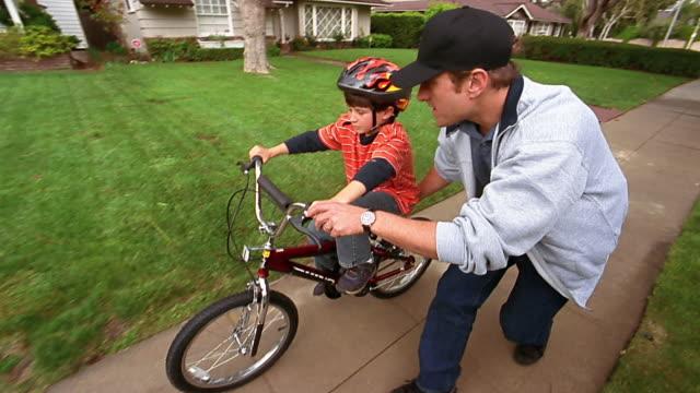 vídeos de stock, filmes e b-roll de a father helps his son ride his bicycle on his own. - acontecimentos da vida