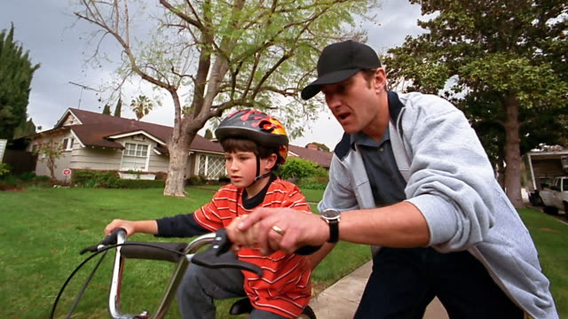 a father helps his son ride his bike on his own. - sports helmet stock videos and b-roll footage