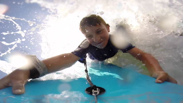 A father helps his son to go body boarding in the waves at the beach. - Slow Motion