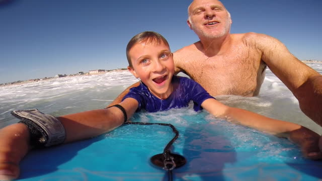 a father helps his son to go body boarding in the waves at the beach. - beach holiday stock videos & royalty-free footage