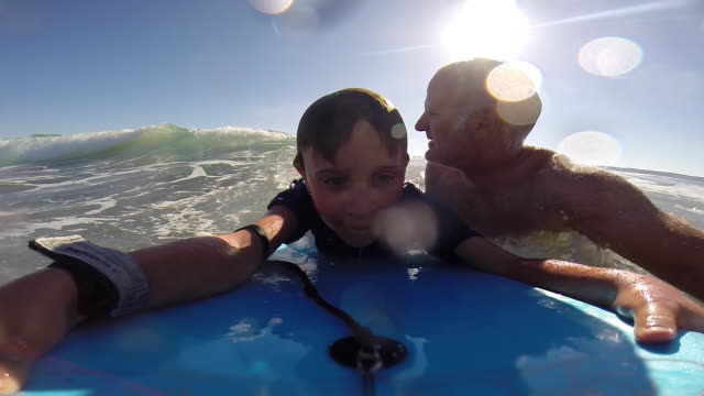 vidéos et rushes de a father helps his son to go body boarding in the waves at the beach. - paradis
