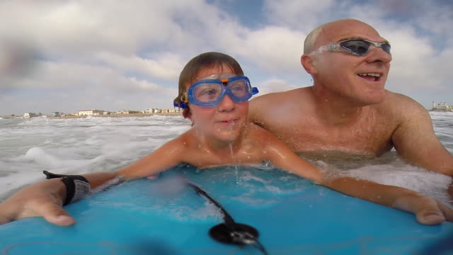 vidéos et rushes de a father helps his son to go body boarding in the waves at the beach while wearing goggles. - slow motion - paradis