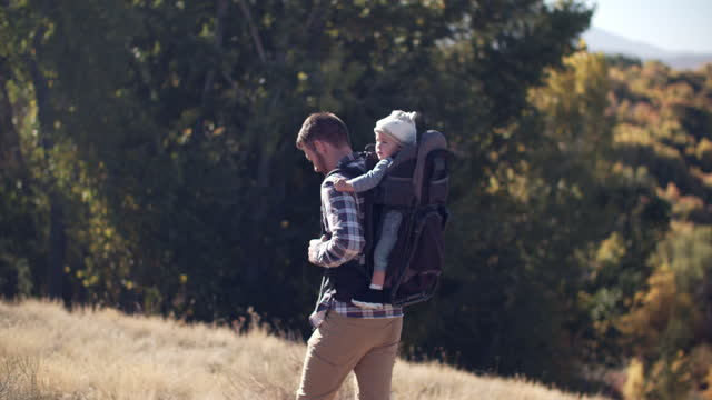 father hiking in the mountains with his baby in a backpack - genderblend stock videos & royalty-free footage