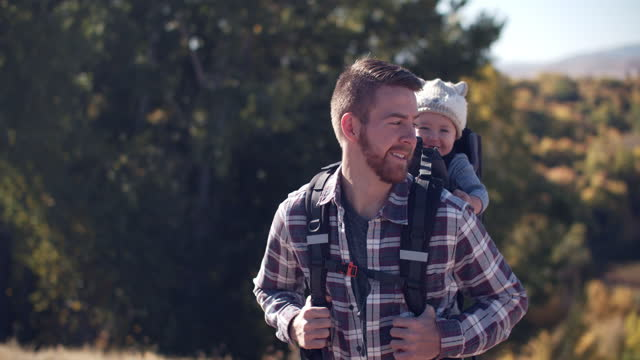 cu father hiking in the mountains with his baby in a backpack - genderblend stock videos & royalty-free footage