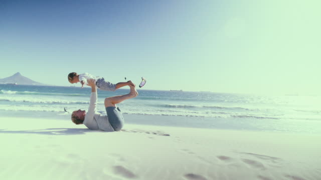 Father holding aloft son on beach