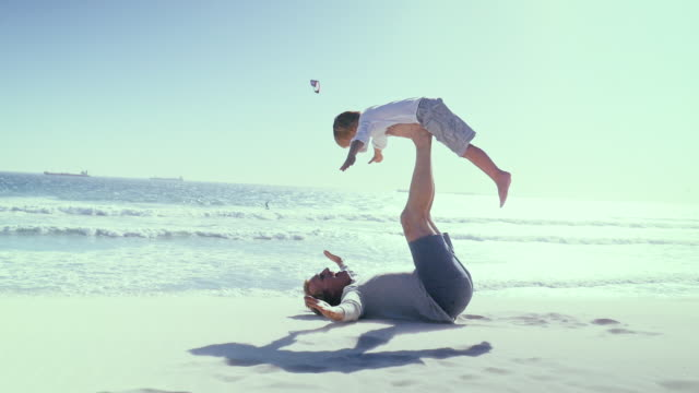Father holding aloft son on beach