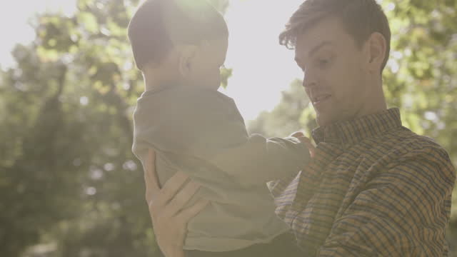 father holding baby boy son in park in autumn on sunny day, father and son togetherness in park lens flare - two generation family stock videos & royalty-free footage