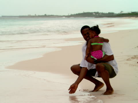 vidéos et rushes de ms,  father holding baby daughter (18-24 months) playing on beach,  harbour island,  bahamas - 18 23 mois
