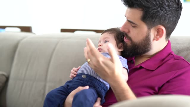father holding baby son at home - pardo brazilian stock videos & royalty-free footage