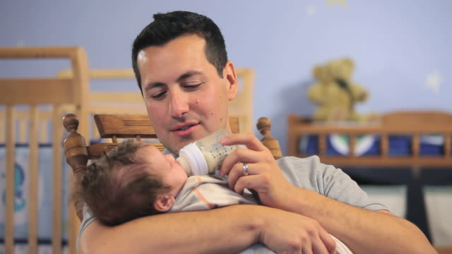 vídeos de stock e filmes b-roll de cu father holding feeding baby boy (2-5 months) from bottle in nursery room / richmond, virginia, usa. - 2 5 meses