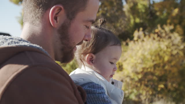 cu father holding his baby girl outdoors - genderblend stock videos & royalty-free footage