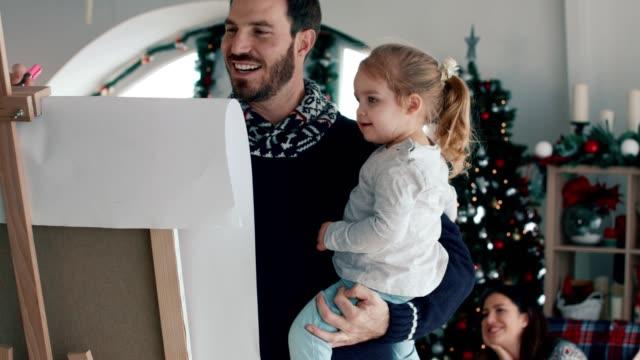 かわいい2歳の娘を抱きしめ、家族と一緒にチャレードを演奏する父 - パントマイム点の映像素材/bロール