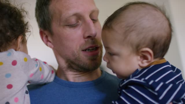 father holding his daughter and baby son - candid stock videos & royalty-free footage