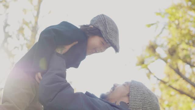 vidéos et rushes de père retenant son fils dans la forêt dans le coucher du soleil au parc de ginkgo. - père