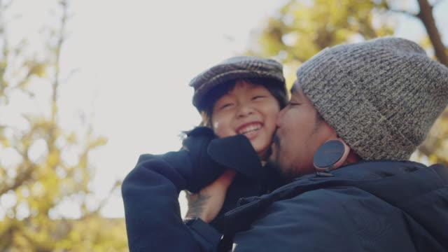 イチョウ公園で夕暮れ時に息子を森に抱く父。 - 抱きしめる点の映像素材/bロール