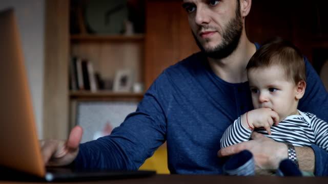 vidéos et rushes de père retenant son fils tout en utilisant l'ordinateur portatif - prendre sur les genoux