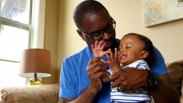 ms zi zo father holding infant son on lap playing clapping game - baby clothing stock videos & royalty-free footage