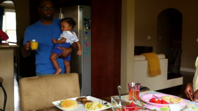 ms ts father holding infant son while carrying glass of juice to daughter at breakfast table - dining table stock videos & royalty-free footage