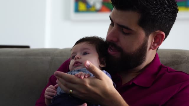 vídeos de stock e filmes b-roll de father holding newborn baby son at home - carinhoso